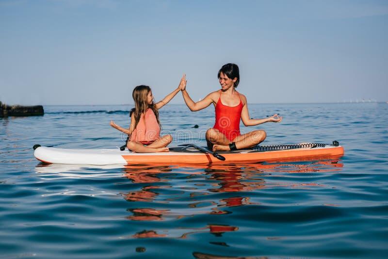 Mamma en weinig dochter die yoga op de peddelraad doen stock foto