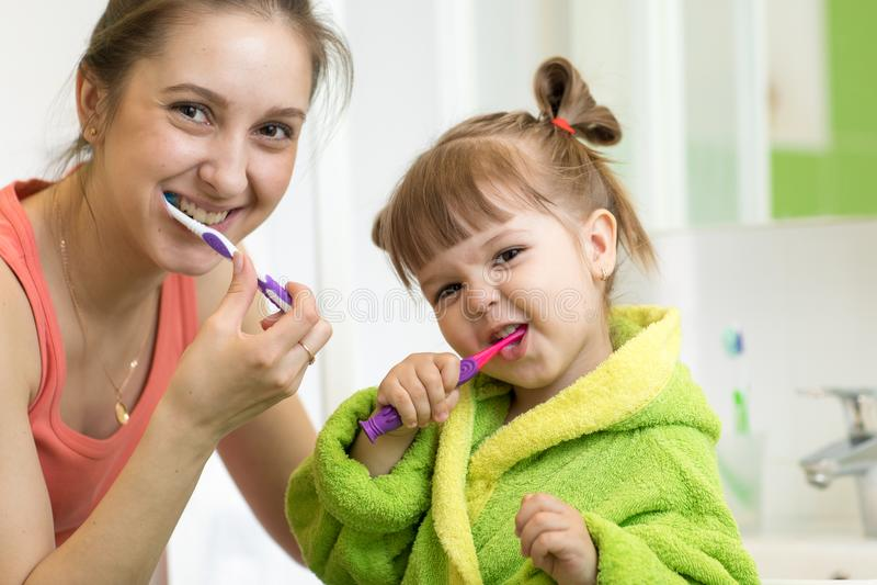 Mamma en weinig jong geitjedochter het borstelen tanden in badkamers stock afbeelding