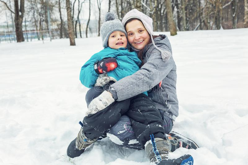 Mamma en weinig zoon die in de sneeuw spelen stock afbeelding