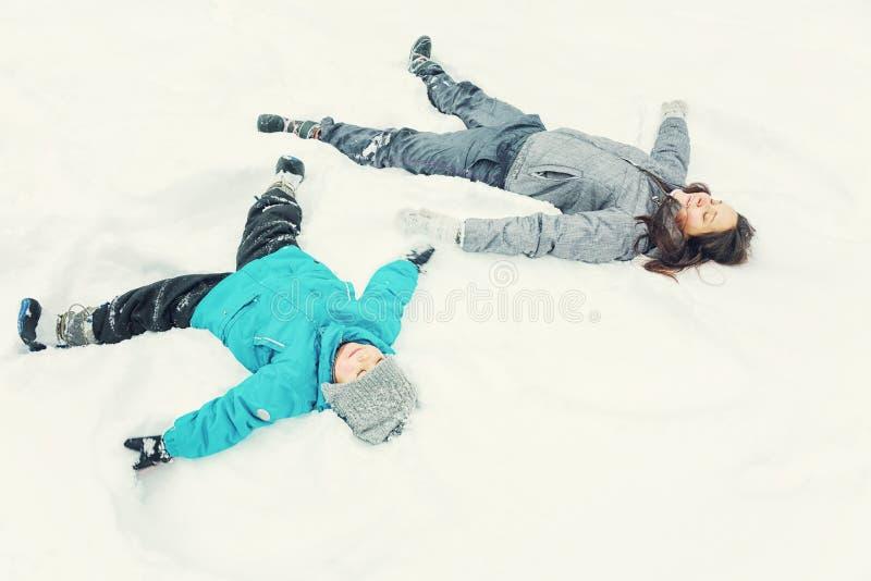 Mamma en weinig zoon die in de sneeuw spelen stock afbeeldingen