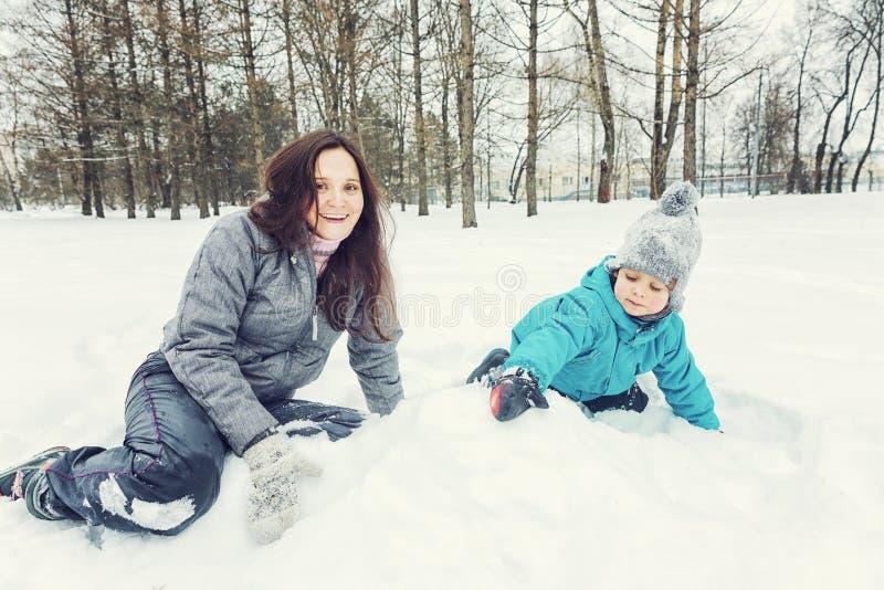 Mamma en weinig zoon die in de sneeuw spelen stock foto's