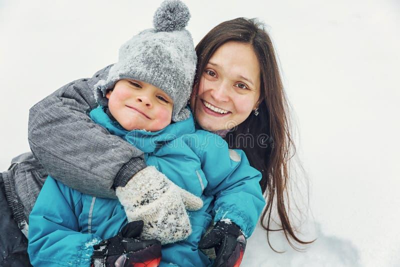 Mamma en weinig zoon die in de sneeuw in de winter spelen stock afbeelding