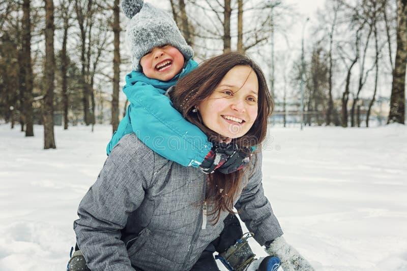 Mamma en weinig zoon die in de sneeuw in de winter spelen stock foto