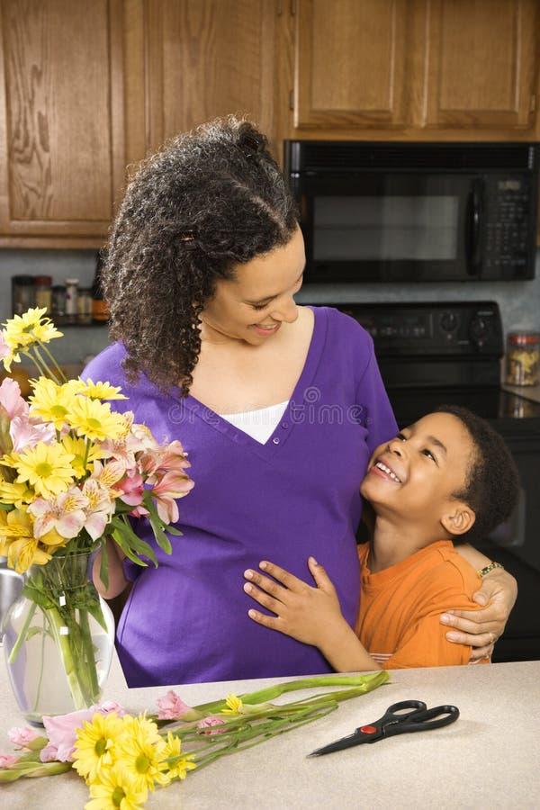 Mamma en zoon die bloemen schikken stock foto