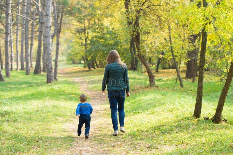 Mamma en zoon die in het park bij zonsondergang lopen stock afbeelding
