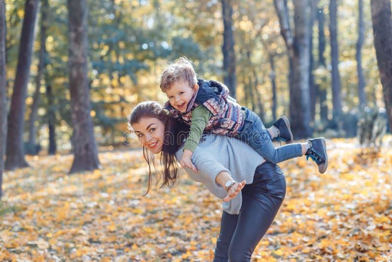 Mamma en zoon die pret in het park in de herfst hebben stock fotografie