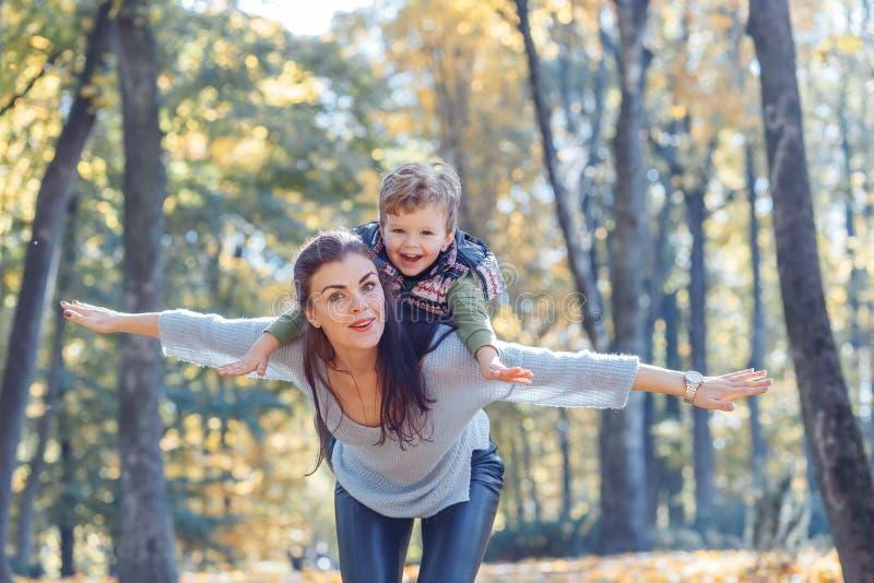 Mamma en zoon die pret in het park in de herfst hebben royalty-vrije stock foto's