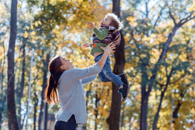 Mamma en zoon die pret in het park in de herfst hebben royalty-vrije stock afbeelding