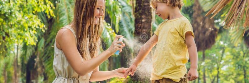 Mamma en zoons de nevel van de gebruiksmug Bespuitend insektenwerend middel op huid openluchtbanner, lang formaat royalty-vrije stock foto's