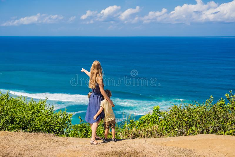 Mamma en zoonsreizigers op een klip boven het strand Leeg paradijs royalty-vrije stock afbeelding