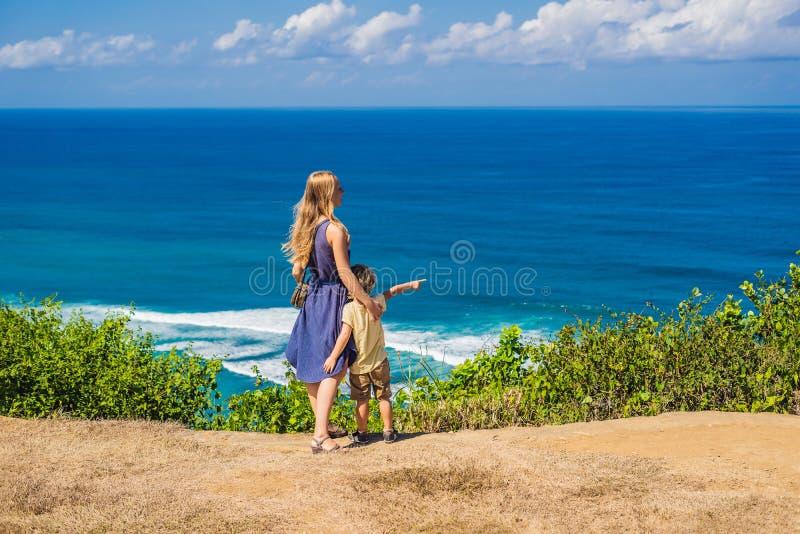Mamma en zoonsreizigers op een klip boven het strand Leeg paradijs royalty-vrije stock fotografie