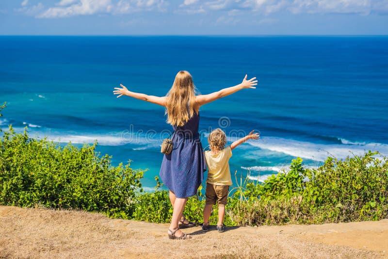 Mamma en zoonsreizigers op een klip boven het strand Leeg paradijs stock fotografie