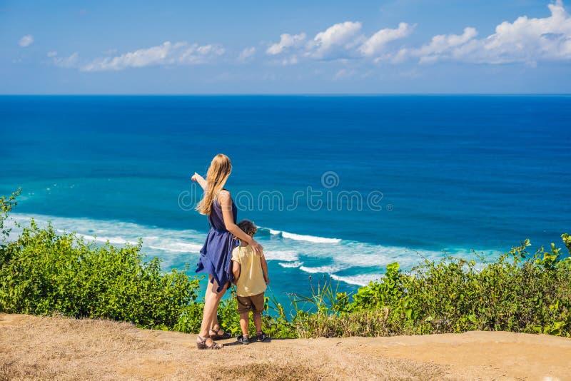 Mamma en zoonsreizigers op een klip boven het strand Leeg paradijs stock foto's