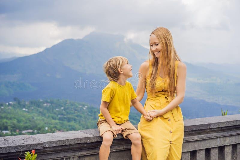 Mamma en zoonstoeristen die op achtergrond Batur-vulkaan bekijken indonesi? Het reizen met jonge geitjesconcept stock foto's
