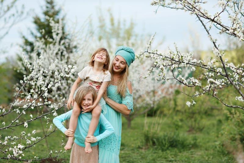 Mamma felice della famiglia e due figlie su un parco della passeggiata in primavera fotografia stock
