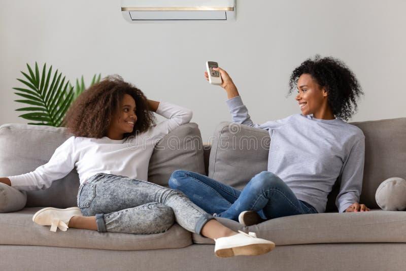 Mamma felice e figlia che si rilassano sullo strato sotto il condizionatore d'aria immagini stock libere da diritti