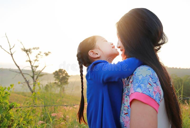 Mamma felice e figlie asiatiche che abbracciano e che baciano nel campo del prato all'alba di mattina immagini stock