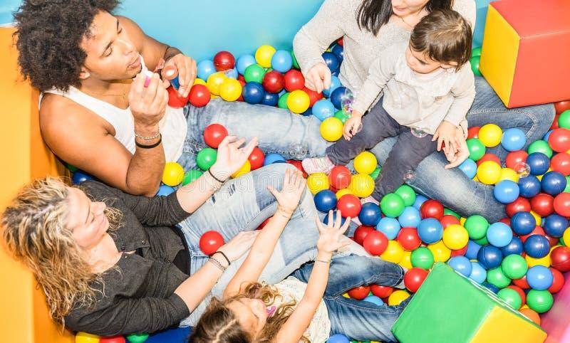 Mamma felice e papà multirazziali che giocano con la figlia al gameroom immagine stock