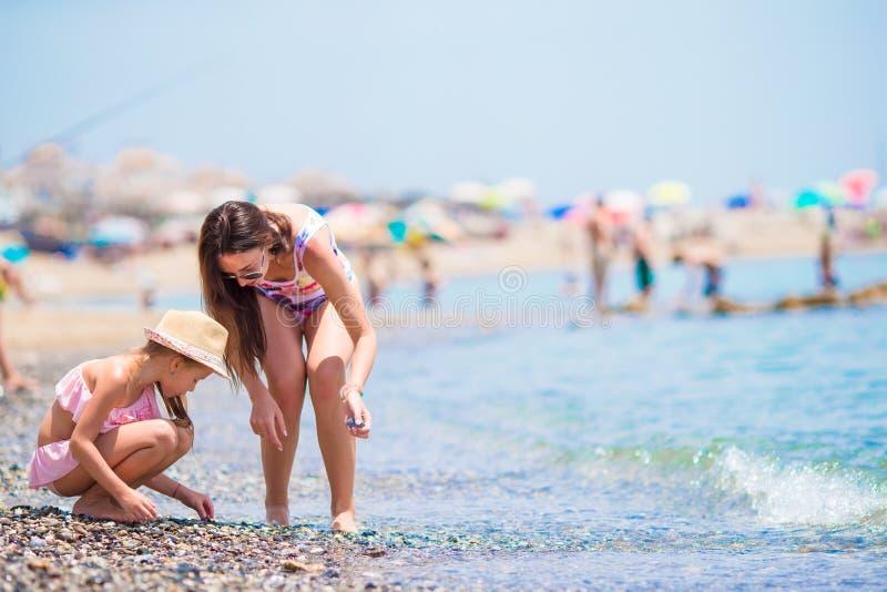 Mamma felice e piccola figlia che godono delle vacanze estive che raccolgono le conchiglie immagini stock