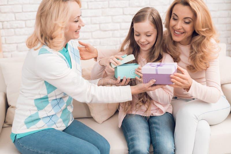 Mamma, grootmoeder en meisje open giftdozen voor de vakantie stock foto
