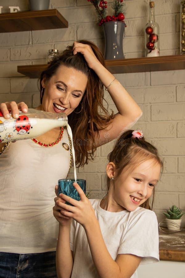 Mamma häller en liten dottermjölk i ett glas arkivfoto
