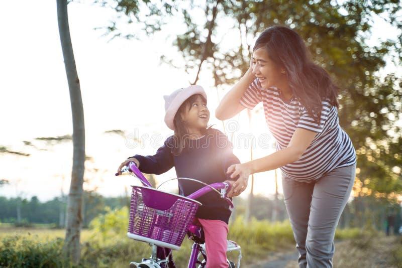 Mamma lär sin barnsdotter att lära sig cyklar royaltyfri foto