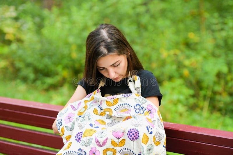 Mamma matar den nyfödda på bench. täckt med en blöjor från bläck. Ung kvinna, ny mor som ammar och tar hand om henne royaltyfria bilder