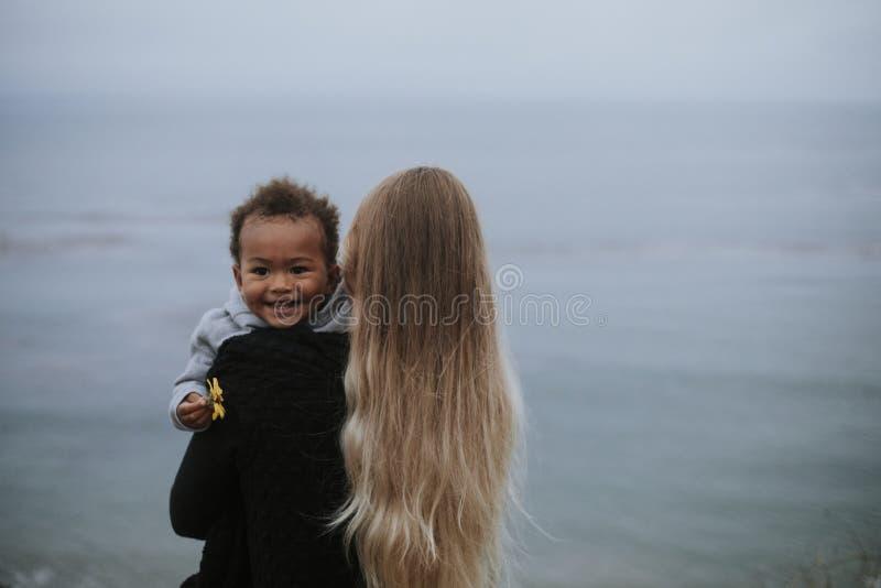 Mamma med den unga sonen vid vattnet arkivfoto