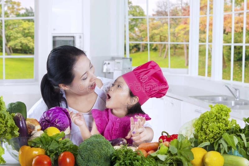 Mamma med dotterkockar i köket royaltyfri foto