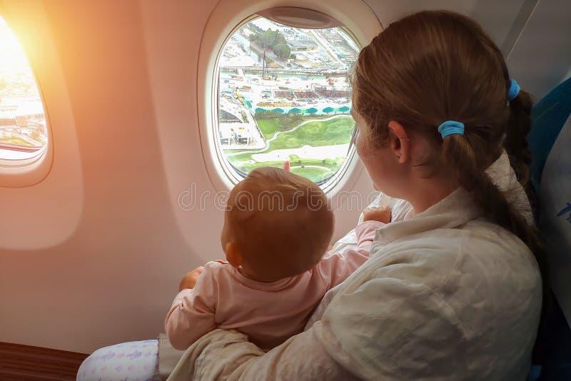 Mamma med en småbarnblick ut fönstret av nivån till jordningen Lopp med den begynnande flickan under ett år arkivbilder