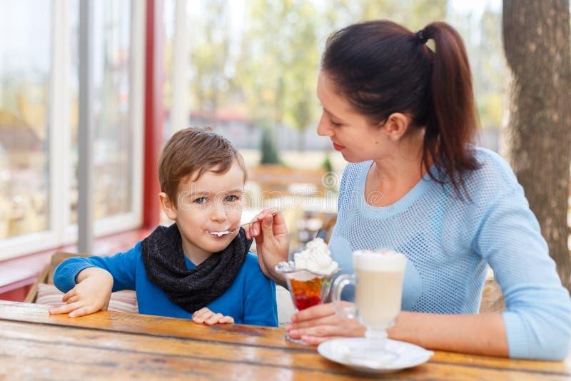 Mamma med ett barn i ett kafé som äter efterrätten arkivbilder