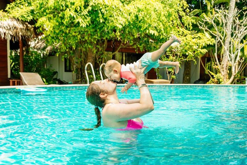 Mamma med ett lyckligt småbarn av åtta månader som har gyckel och simmar i pölen Den unga kvinnan som kysser henne, behandla som  arkivbild