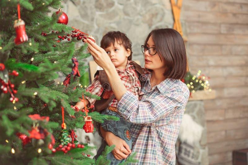 Mamma med lilla barnet i skandinavisk julinre royaltyfria foton