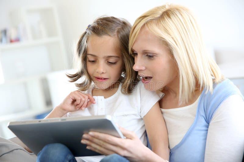Mamma med lilla flickan som använder minnestavlan royaltyfri foto