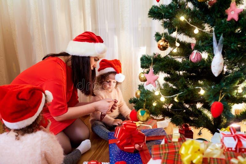 Mamma med unga flickor som får klara för jul i rumintelligensen royaltyfri fotografi