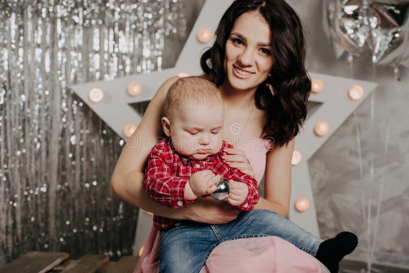 Mamma met de pasgeboren zoon van de babyjongen in haar wapens op de achtergrond van Kerstmisdecor stock fotografie