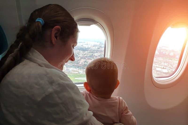 Mamma met een kleine baby in haar wapens die op het vliegtuig vliegen Zij kijken uit het venster op de stad met rente die met zui stock afbeelding