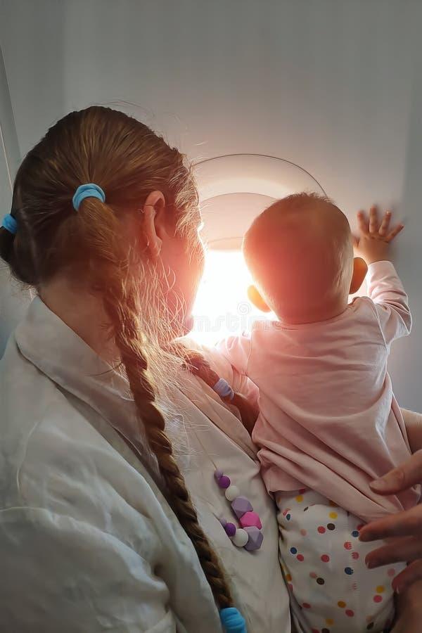 Mamma met een kleine baby in haar wapens die op het vliegtuig vliegen Zij kijken uit het venster met renteverticaal stock afbeeldingen