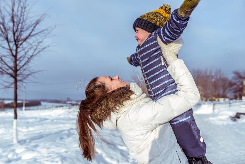 Mamma met een kleine zoon 3 jaar oude, zonnige dag in de winter buiten in het park Spel in de verse lucht Gelukkige glimlachende  stock afbeelding