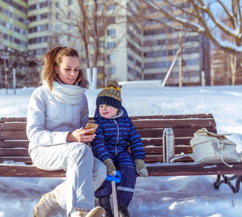 Mamma met een kleine zoon 3 jaar oude, zonnige dag in de winter buiten in het park Zit op een bank in de handen van een smartphon stock foto's