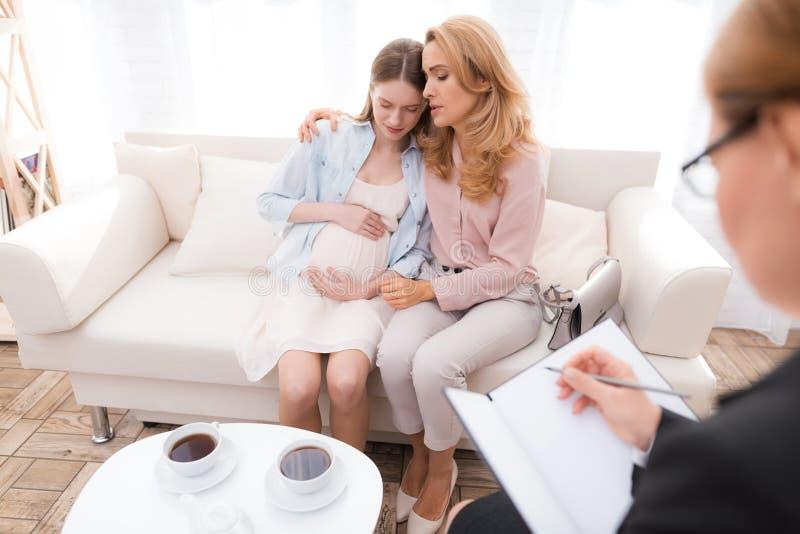 Mamma met een zwangere tiener bij een psycholoog` s ontvangst stock foto's