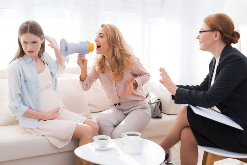 Mamma met een zwangere tiener bij een psycholoog` s ontvangst royalty-vrije stock afbeeldingen