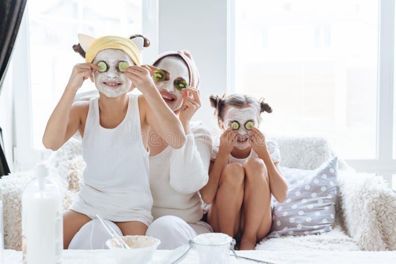 Mamma met haar dochters die het masker van het kleigezicht maken stock afbeeldingen