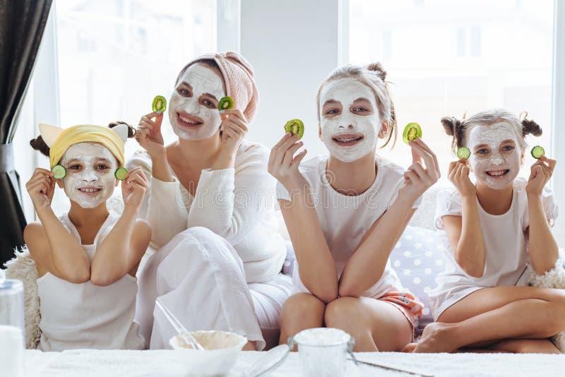 Mamma met haar dochters die het masker van het kleigezicht maken royalty-vrije stock fotografie