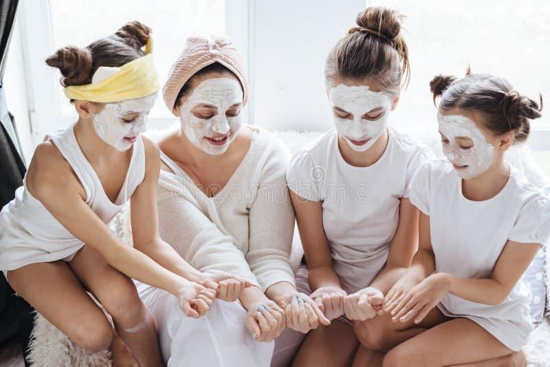 Mamma met haar dochters die het masker van het kleigezicht maken stock foto's