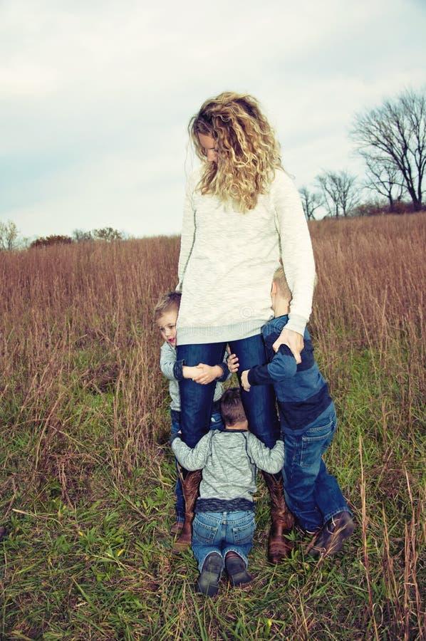 Mamma met kinderen die op haar hangen royalty-vrije stock afbeelding