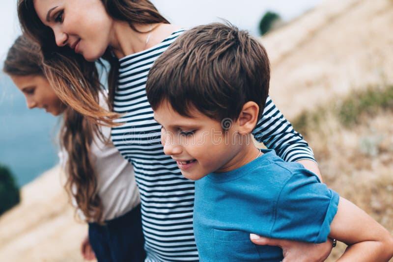 Mamma met kinderen openlucht lopen stock foto's