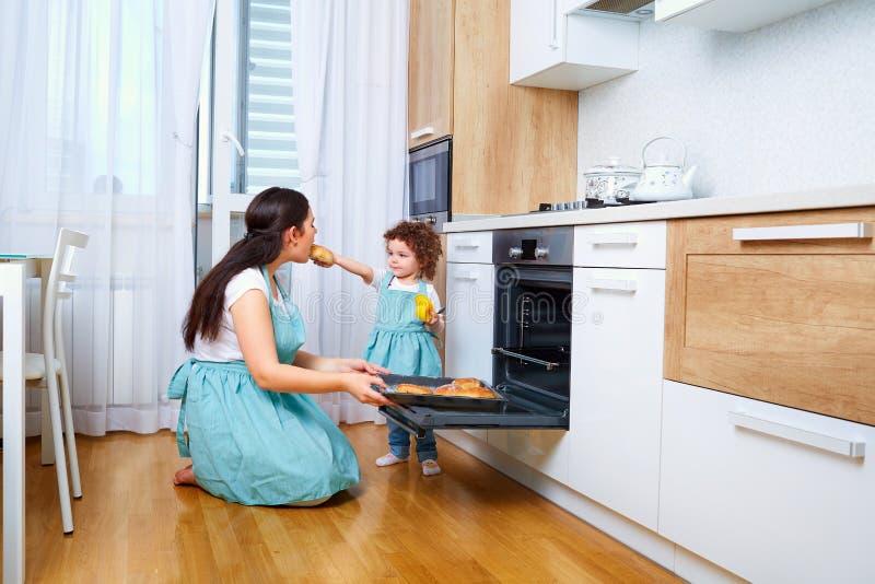 Mamma met krullende dochter in de keuken die op zijn plaats voorbereidingen treffen B royalty-vrije stock foto's