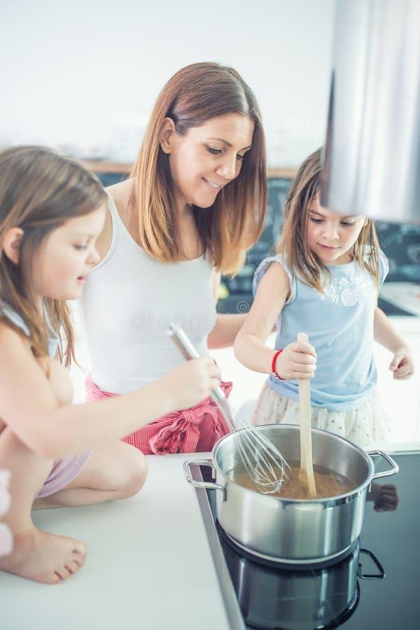 Mamma met twee jonge tweelingendochters in de keuken kokende spaghetti royalty-vrije stock fotografie