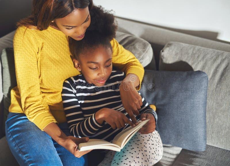 Mamma nera che impara figlia per leggere immagini stock